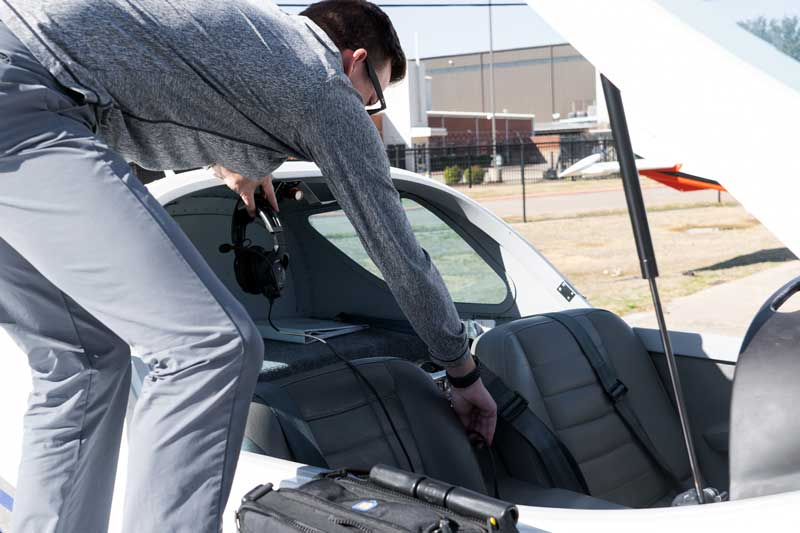 flight instructor reaching into airplane